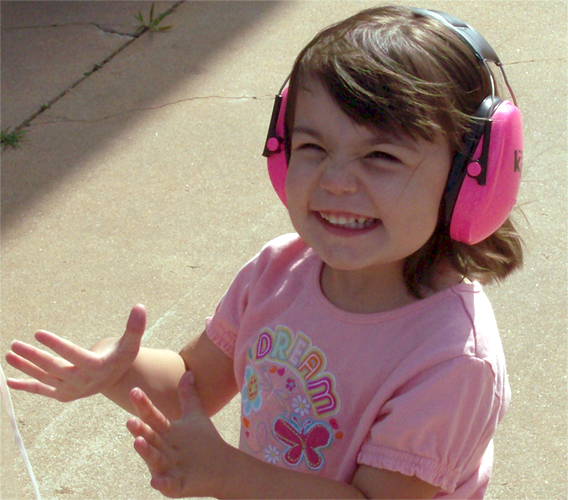 Destiny, wearing pink ear muffs for children, 2 years old.